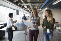 Creative businesswomen with laptop walking in open plan office with businessmen playing ping pong in background 11096065539| 写真素材・ストックフォト・画像・イラスト素材|アマナイメージズ