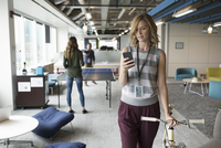 Businesswoman with smart phone walking with bicycle in office while colleagues play ping pong in background 11096065543| 写真素材・ストックフォト・画像・イラスト素材|アマナイメージズ