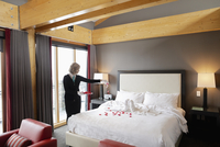 Female room service hotel staff sprinkling roses on bed in luxury hotel room
