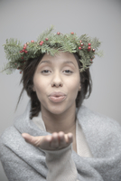 Portrait beautiful young brunette Jamaican woman wearing Christmas wreath on head and blowing a kiss