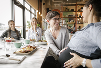 Happy woman touching pregnant friend's belly at restaurant table