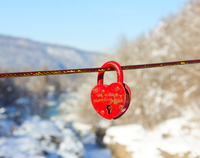 old closed red padlock in heart shape on a background of a winter mountain landscape close up 11098100268| 写真素材・ストックフォト・画像・イラスト素材|アマナイメージズ