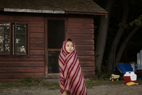 Girl (8-9) wrapped in blanket standing in front of log cabin 11100001648| 写真素材・ストックフォト・画像・イラスト素材|アマナイメージズ