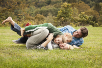 Family wrestling with children (2-3) (6-7) on grass