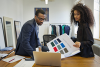 Fashion designers reviewing fabric swatches by laptop 11100012041| 写真素材・ストックフォト・画像・イラスト素材|アマナイメージズ