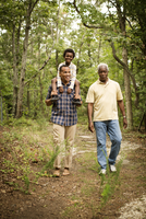 Portrait of boy (6-7) with his father and grandfather in forest
