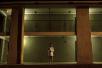 Young woman standing outside motel in nightgown 11100019723| 写真素材・ストックフォト・画像・イラスト素材|アマナイメージズ