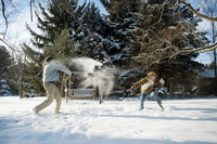 Teenage boy (16-17) having snowball fight with friend