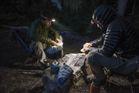 USA, Washington State, Mt. Rainier National Park, Teenage boy (14-15) playing cards with friend in forest