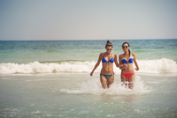 USA, Florida, Pensacola, Two young women running in water