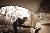 Woman doing exercises next to wall in tunnel