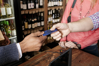 High angle view of owner taking credit card from customer at wine shop 11100034066| 写真素材・ストックフォト・画像・イラスト素材|アマナイメージズ