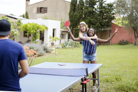 Cheerful women playing table tennis with male friend at yard 11100035392| 写真素材・ストックフォト・画像・イラスト素材|アマナイメージズ