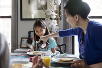 Mother pouring maple syrup on pancakes for daughter during breakfast 11100036222| 写真素材・ストックフォト・画像・イラスト素材|アマナイメージズ