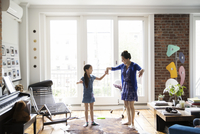 Girl and mother holding hands and dancing on carpet at home 11100036246| 写真素材・ストックフォト・画像・イラスト素材|アマナイメージズ