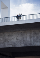 Low angle view of men standing on bridge in city against sky 11100036866| 写真素材・ストックフォト・画像・イラスト素材|アマナイメージズ