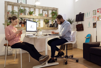 Male illustrator working while female colleague using smart phone in creative office 11100037561| 写真素材・ストックフォト・画像・イラスト素材|アマナイメージズ