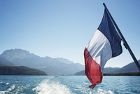 French flag over Lake Annecy against clear sky 11100038281| 写真素材・ストックフォト・画像・イラスト素材|アマナイメージズ