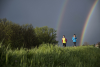 Friends running on grassy field against sky with double rainbow 11100039982| 写真素材・ストックフォト・画像・イラスト素材|アマナイメージズ