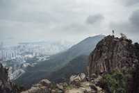 Distant view of man standing on mountain by cityscape during foggy weather 11100040140| 写真素材・ストックフォト・画像・イラスト素材|アマナイメージズ
