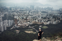High angle view of man looking at cityscape while standing on rock 11100040141| 写真素材・ストックフォト・画像・イラスト素材|アマナイメージズ