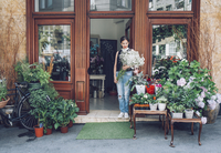 Female florist holding white flowers while standing entrance of shop 11100040784| 写真素材・ストックフォト・画像・イラスト素材|アマナイメージズ