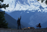 Man with arm raised standing against snowcapped mountain