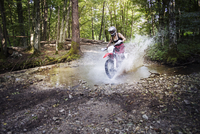 Young female biker riding dirt bike on puddle in forest 11100044293| 写真素材・ストックフォト・画像・イラスト素材|アマナイメージズ