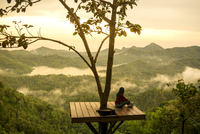Woman sitting on observation point and looking at view 11100048469| 写真素材・ストックフォト・画像・イラスト素材|アマナイメージズ