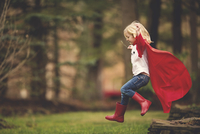 Happy girl wearing cape running against trees at forest 11100050382| 写真素材・ストックフォト・画像・イラスト素材|アマナイメージズ