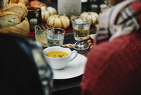 Woman having pumpkin soup while sitting at table in backyard 11100050627| 写真素材・ストックフォト・画像・イラスト素材|アマナイメージズ