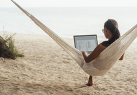 Woman using laptop computer while relaxing on hammock at beach 11100051895| 写真素材・ストックフォト・画像・イラスト素材|アマナイメージズ