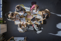 Overhead view of students studying at table in classroom