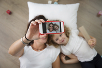 Overhead view of mother and daughter taking selfie through smart phone while lying on floor at home 11100055919| 写真素材・ストックフォト・画像・イラスト素材|アマナイメージズ
