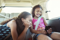 Girls looking at smart phone while traveling in car 11100057253| 写真素材・ストックフォト・画像・イラスト素材|アマナイメージズ
