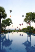 Hot air balloons and palm trees reflecting in swimming pool at Bagan 11100058612| 写真素材・ストックフォト・画像・イラスト素材|アマナイメージズ