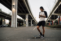 Man using mobile phone while standing with skateboard on street 11100059693| 写真素材・ストックフォト・画像・イラスト素材|アマナイメージズ