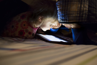 Siblings using tablet computer on bed in darkroom at home 11100059946| 写真素材・ストックフォト・画像・イラスト素材|アマナイメージズ