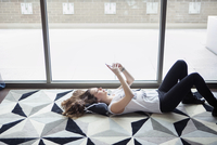 Young woman using smart phone while lying on carpet by window at home