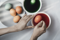 Cropped hands of woman making Easter eggs with dye at home