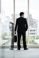 Rear view of businessman looking through window while standing in office 11100061926| 写真素材・ストックフォト・画像・イラスト素材|アマナイメージズ
