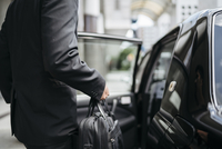 Midsection side view of businessman entering taxi on city street 11100061928| 写真素材・ストックフォト・画像・イラスト素材|アマナイメージズ