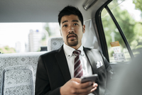 Young businessman holding smart phone while sitting in taxi 11100061929| 写真素材・ストックフォト・画像・イラスト素材|アマナイメージズ