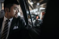 Thoughtful businessman looking through window in taxi 11100061934| 写真素材・ストックフォト・画像・イラスト素材|アマナイメージズ