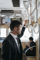 Side view of thoughtful businessman standing in train 11100061935| 写真素材・ストックフォト・画像・イラスト素材|アマナイメージズ