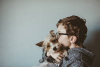 Side view of boy kissing Yorkshire Terrier against wall at home