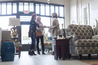 Woman looking at owner doing handshake with friend in furniture store 11100063276| 写真素材・ストックフォト・画像・イラスト素材|アマナイメージズ