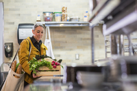 Female chef with crate of vegetables standing at kitchen counter in restaurant 11100063347| 写真素材・ストックフォト・画像・イラスト素材|アマナイメージズ