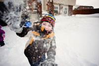 Portrait of happy boy playing with snow in yard