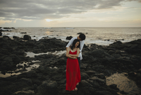 Happy couple embracing while standing at beach against sky during sunset 11100064351| 写真素材・ストックフォト・画像・イラスト素材|アマナイメージズ